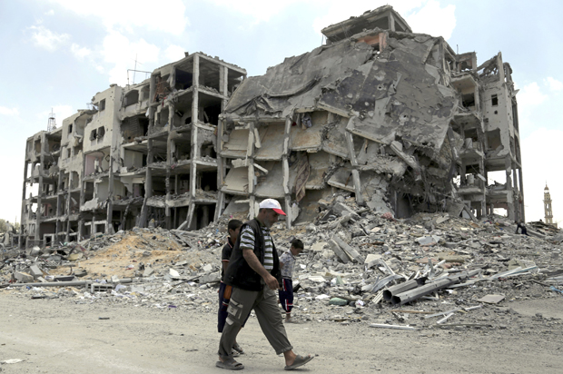 Palestinians walk in front of the rubble of buildings destroyed in Israeli strikes, in Beit Lahiya, northern Gaza Strip, Monday, Aug. 4, 2014. (AP Photo/Adel Hana)