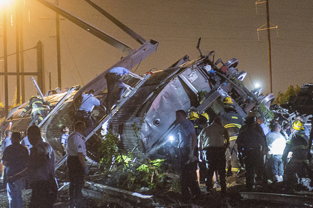 Rescue workers search for victims in the wreckage of a derailed Amtrak train in Philadelphia, Pennsylvania May 12, 2015.  An Amtrak passenger train with more than 200 passengers on board derailed in north Philadelphia on Tuesday night, killing at least five people and injuring more than 50 others, several of them critically, authorities said. Authorities said they had no idea what caused the train wreck, which left some demolished rail cars strewn upside down and on their sides in the city's Port Richmond neighborhood along the Delaware River. REUTERS/Bryan Woolston      TPX IMAGES OF THE DAY      - RTX1CPFO