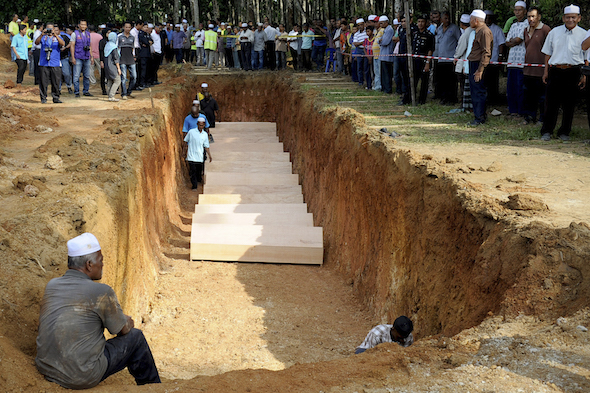 Malaysian religious officers and villagers places coffins containing remains of Rohingya migrants for a mass burial ceremony in Kedah, Malaysia on Monday, June 22, 2015. (AP Photo/Gary Chuah)