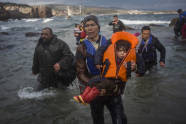 Refugees and migrants make their way out of the sea, as their boat, on which they crossed a part of the Aegean sea from Turkey, hit on rocks on the Greek island of Lesbos, on Saturday, Dec. 12, 2015. Any link between extremism and the thousands of people fleeing violence in Syria and elsewhere is false, a top European human rights official said Friday, noting that those who have perpetrated recent attacks in Europe were citizens of European countries.(AP Photo/Santi Palacios)