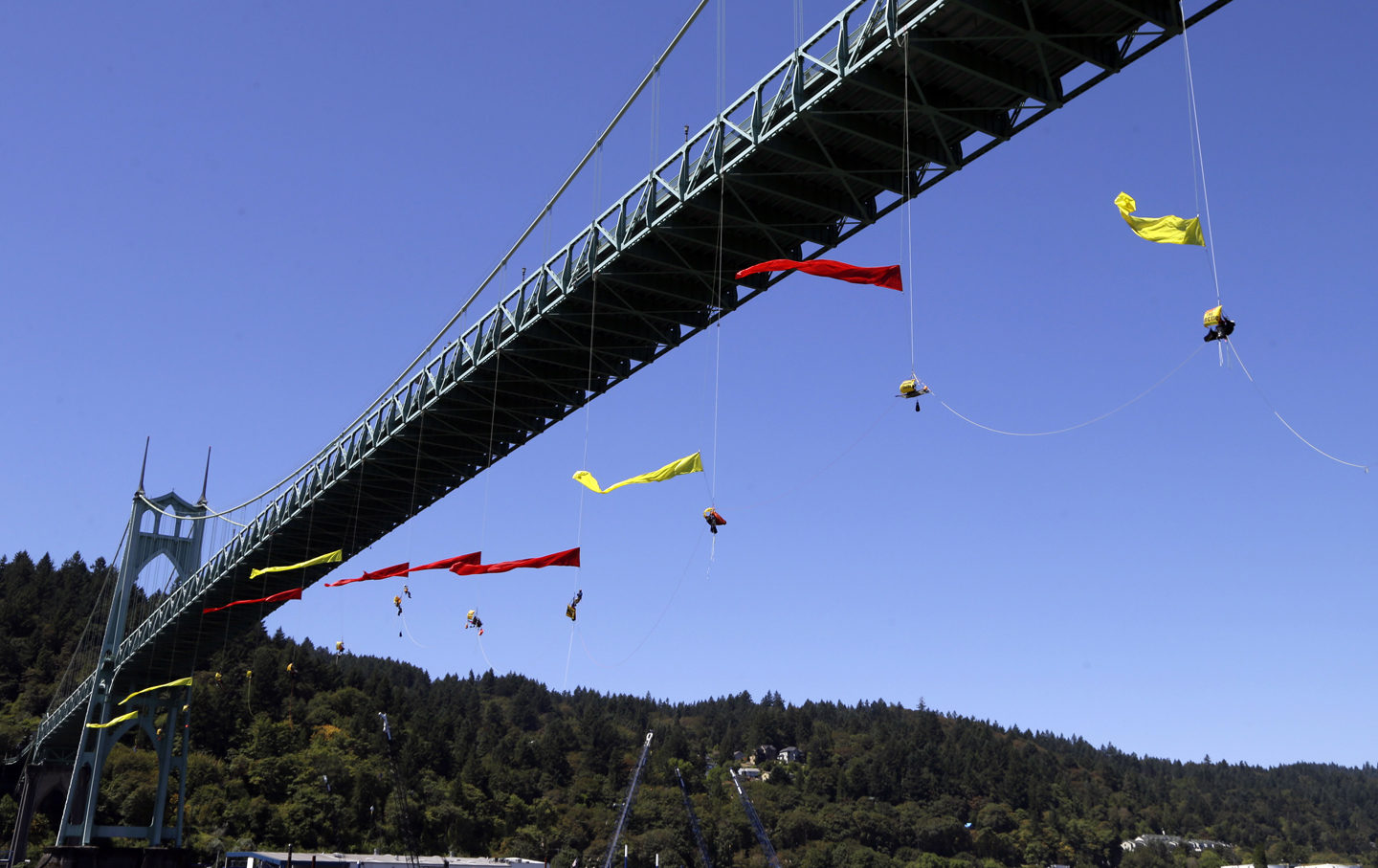 Activists unfurl colored banners while hanging from the St. Johns bridge in Portland, Ore., Wednesday, July 29, 2015, to protest  the departure of Royal Dutch Shell PLC icebreaker Fennica, which is in Portland for repairs. The icebreaker is a vital part of Shell's exploration and spill-response plan off Alaska's northwest coast. Greenpeace officials say  the activists have enough water and food to last for days, and can hoist themselves to allow other marine traffic to pass. (AP Photo/Don Ryan)