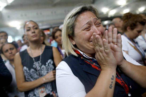 A woman reacts as Family members, colleagues and friends of the victims of Tuesday blasts gather for a memorial ceremony at the Ataturk Airport in Istanbul, Thursday, June 30, 2016. A senior Turkish official on Thursday identified the Istanbul airport attackers as a Russian, Uzbek and Kyrgyz national hours after police carried out sweeping raids across the city looking for Islamic State suspects. Tuesday's gunfire and suicide bombing attack at Ataturk Airport killed dozens and injured over 200. Turkish authorities have banned distribution of images relating to the Ataturk airport attack within Turkey.(AP Photo/Emrah Gurel)