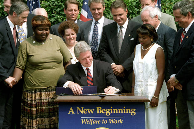 President Bill Cllinton signs into law a bill reforming welfare which ends the 61 year-old federal guarantee of aid to the poor in Washington, August 22, 1996. With the President, L-R, are Delaware Governor Thomas Carper, former welfare mothers Lillie Harden and Janet errel, Vice President Al Gore, West Virginia Governor Gaston Caperton, Senator John Breaux (D-LA) and former welfare mother Penelope Howard. REUTERS/Stephen Jaffe AS - RTRKPG