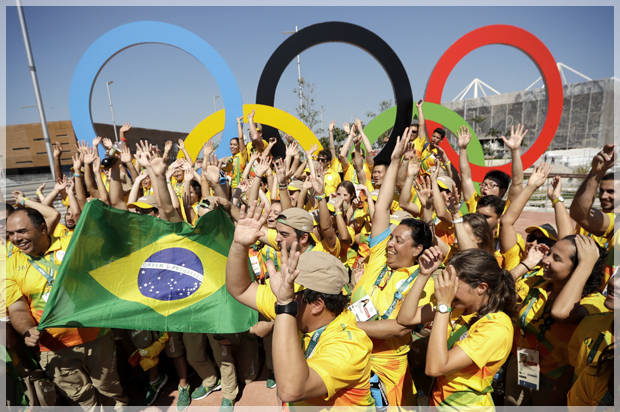 Volunteers cheer around a set of Olympic rings at the Olympic Park in Rio de Janeiro, Brazil, Monday, Aug. 1, 2016. The Summer 2016 olympics is scheduled to open Aug. 5. (AP Photo/Charlie Riedel)